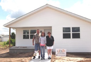 Delbert McGuirk, Shandie Reed and Jackie McGuirk in front of their newly built home.