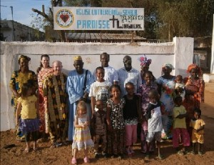 "Parishioners pose in front of a new church sign. This is a new level of ""visibility"" for the parish in Linguere, and we are thankful to be in a country where a minority religion can express itself without fear."