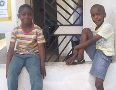 Two boys in the after-school program wait near the kitchen for lunch.